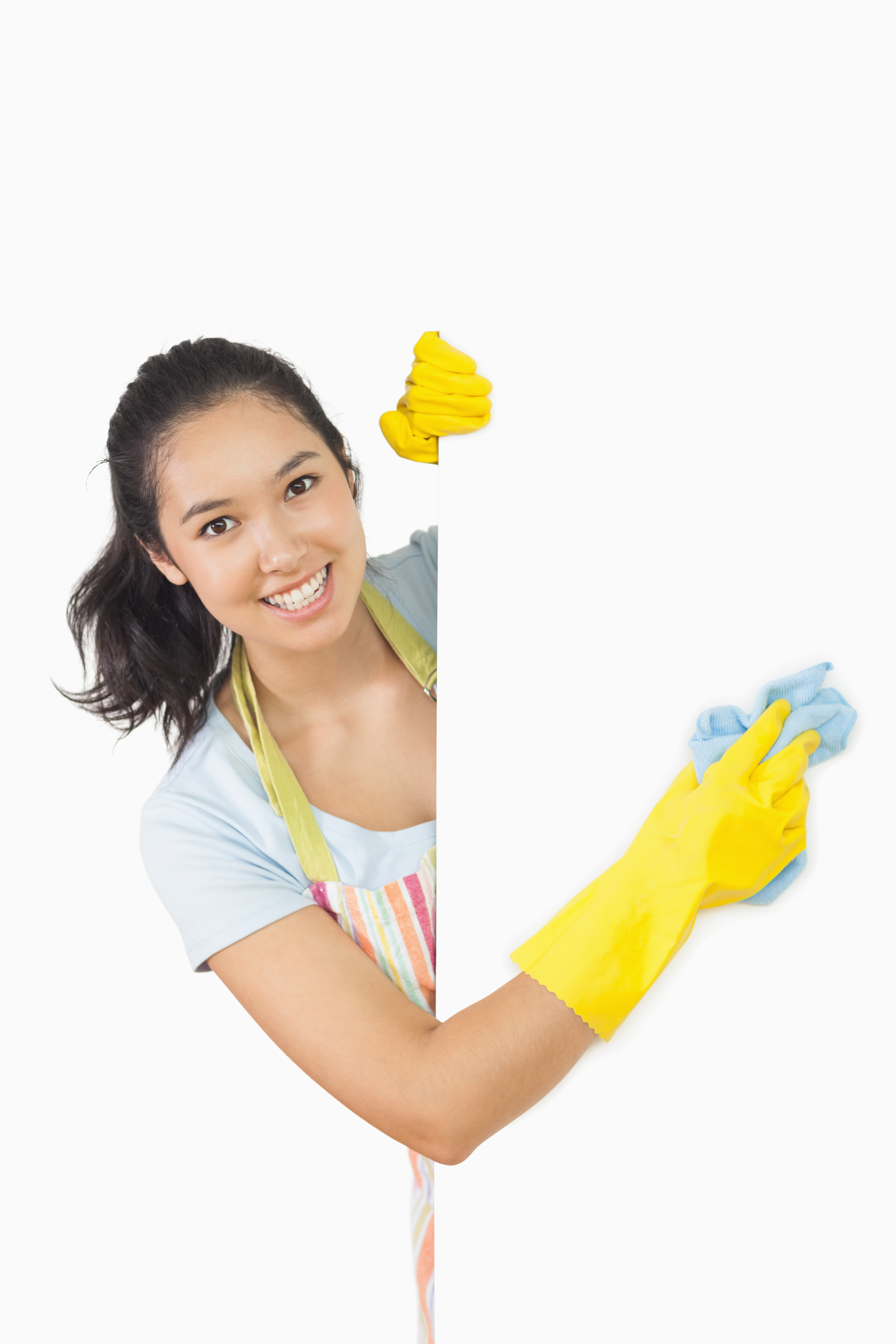 Smiling woman in apron and rubber gloves cleaning white surface